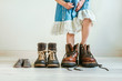 canvas print picture - Close up of little girl in  dress putting on fathers hiking shoes