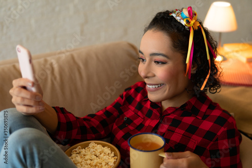 Fototapeta Happy cheerful Young brazilian woman with tea mug watching video on mobile smart phone Indoors at home living room. Entertainment, recreation, live stream concept. obraz