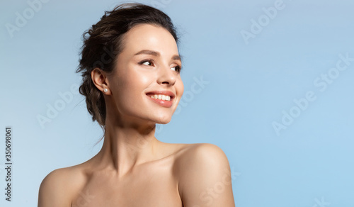 Fotografia Toothy smiling young woman with shiny glowing perfect facial skin and bare shoulder looking aside