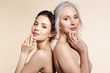 Elderly and young women with smooth skin and natural makeup standing back-to-back.