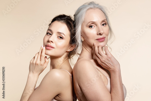 Elderly and young women with smooth skin and natural makeup standing back-to-back Canvas