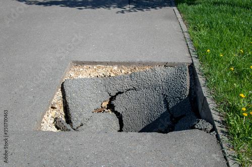 Fototapeta Dangerous deep hole in the asphalt in summer