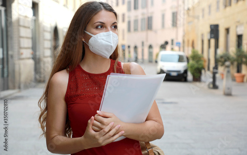 Fototapeta COVID-19 Global Economic Crisis Unemployed Worried Girl with KN95 FFP2 Mask  Looking for Job Walking in City Street Delivering Curriculum Vitae obraz