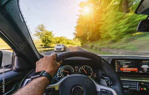 Obraz hands of car driver on steering wheel, road trip, driving on highway road - fototapety do salonu