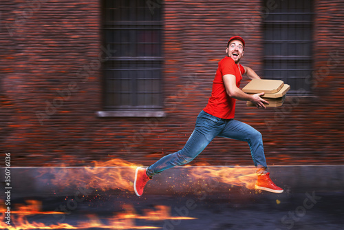 Obraz Courier runs fast to deliver quickly pizzas with fiery feet. Cyan background - fototapety do salonu