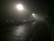 Leinwandbild Motiv Cars In Parking Lot By Illuminated Empty Road At Night