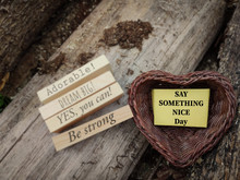 Motivational And Inspirational Celebration Concept - SAY SOMETHING NICE Day Text On Notepaper Inside Heart Shaped Basket