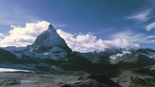 Beautiful Mountain Ranges And Open Landscapes With The Snowy Matterhorn Mountain Peak With Clouds In The Clear Sky On An Afternoon In Switzerland, Europe  - Tracking Aerial Drone Shot