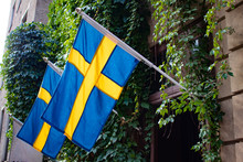 Two Swedish Flags Hang Outside Of An Ivy Covered Building In The Gamla Stan Neighborhood Of Stockholm, Sweden