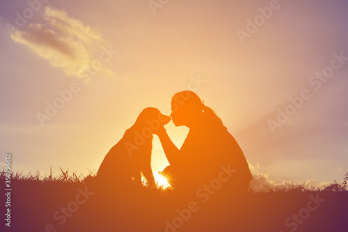 Fotografia Silhouette Girl With Dog Sitting On Field Against Sky During Sunset