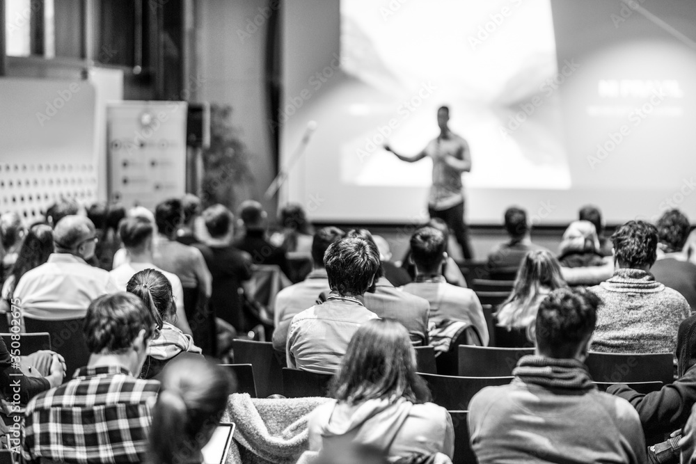 Fototapeta Speaker giving a talk in conference hall at business event. Audience at the conference hall. Business and Entrepreneurship concept. Focus on unrecognizable people in audience. Black and white image.