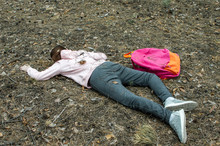 Murder In The Woods.The Body Of A Teenage Girl In A Tracksuit Lies On The Ground In The Woods. Victim Of Violence. The Concept Of Child Abduction. Horizontal Photo.