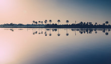 Scenic View Of Reflection Of Trees In Lake Against Sky During Sunset