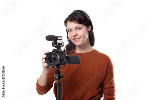 Obraz na plátně Female art student studying to be a filmmaker using a camera on a tripod for a project