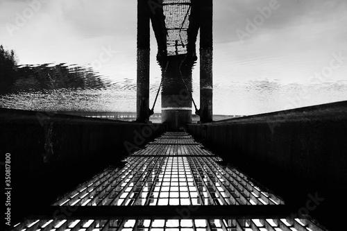 Upside Down Image Of Footbridge Reflecting In Water Fototapet