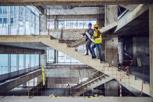 Construction Worker And Main Architect Climbing The Stairs And Talking About Progress In Construction Of New Building.