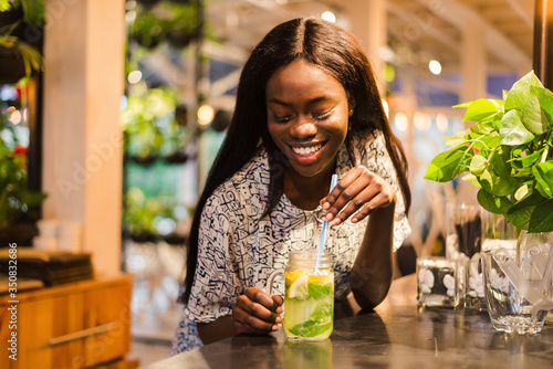 African Woman drinking lemonade with a straw, in a restaurant Fototapeta