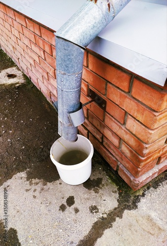 Fényképezés A white bucket stands under a drainpipe on the brick wall of the house
