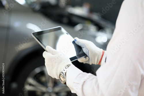 Fotografija Man holds tablet near car for troubleshooting