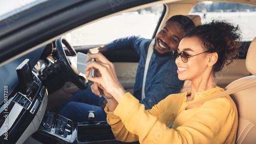 Fototapeta African American Couple Making Selfie Sitting In New Car, Panorama obraz