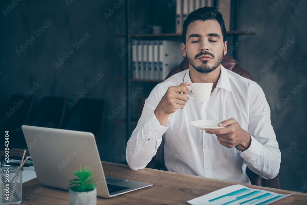 Fototapeta Portrait of his he nice attractive chic classy confident man sitting in chair having rest drinking caffeine beverage enjoying at modern loft industrial style interior work place station indoors