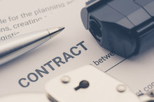 Pen, A Pistol And A Handcuff On A Contract Form, Depicting A Contract Was Signed By A Coerced Or Forced Person At Gunpoint.