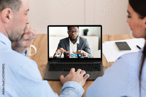 Photo Workers having discussion during video call with colleague