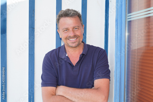 Photo Outdoor happy handsome man arms crossed in white blue wooden hut background in a