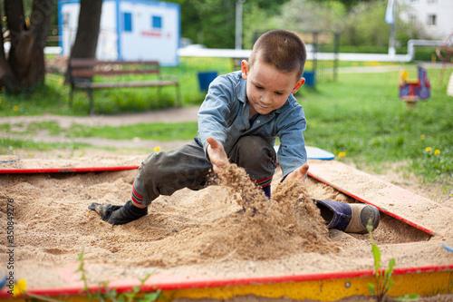 Obraz na plátně The child plays in the sandbox.