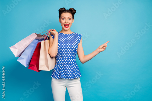 Fototapeta Photo of pretty excited lady hold many packs addicted shopaholic indicating finger empty space advising low prices wear dotted blouse white pants isolated blue color background obraz