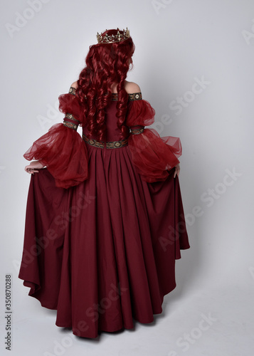 Fotografiet Portrait of a beautiful woman with red hair wearing  a  flowing Burgundy fantasy gown and golden crown