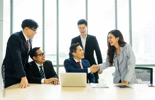 Asian business male and female smiling shake hands with congratulation Wallpaper Mural