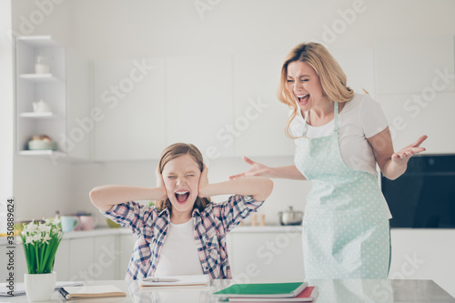 Fototapeta Photo of two people crazy furious mother shout her small daughter sit table cant write essay avoid close cover ears palms yell wear dotted apron in house kitchen indoors obraz