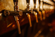 Details Of The Beer Bar. Beer Taps In A Row In Perspective. Warm Tinting, Different Focus.  Close Up Of Beer Tap. Selective Focus.