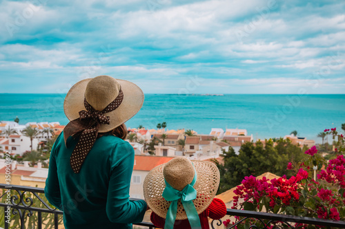 mother and daughter looking at scenic view from the balcony
