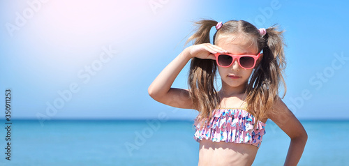 Banner with cute little girl has fun on the beach.