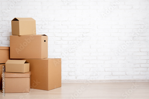 Foto moving day concept - cardboard boxes and copy space over white brick wall