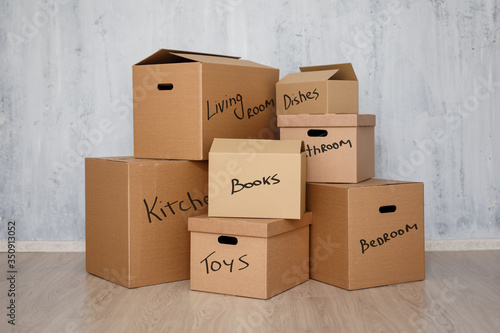 Obraz moving day - brown cardboard boxes with belongings stacked over gray background - fototapety do salonu