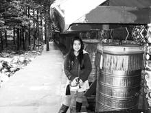Portrait Of Smiling Girl Standing By Tibetan Prayer Wheels On Footpath