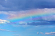 canvas print picture - Rainbow in the blue sky with clouds over sea