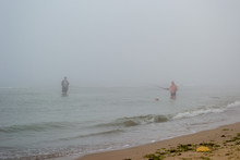 Fishermen Catch Fish In The Fog On The Beach