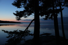 Dramatic Sunset Overlooking Distant Water Reflections From Nearby Islands While Camping On A Beach Under The Shelter From Large Trees.