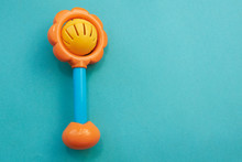 Plastic Toy Rattle In Bright Yellow Color With A Blue Handle. Plastic Retro Rattle. Baby Toys On Blue Background. Flat Lay. Copy Space.