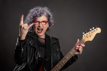 Close Up Portrait Of Beautiful Old Woman Playing Electric Guitar On A Gray Background