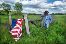 Man Wearing Cowboy Hat Walking In Grassy Agricultural Field With American Flag Hanging On Barbwire Fence
