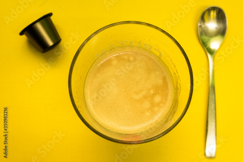 Stampa su Tela Coffee cup with a spoon and brown capsule on a yellow Surface / Vaso de café con