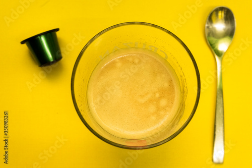 Fotografia Coffee cup with a spoon and green capsule on a yellow Surface / Vaso de café con