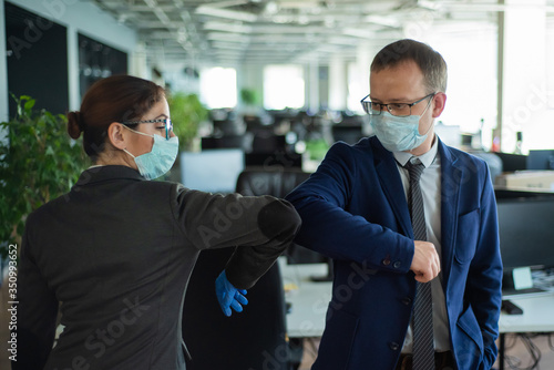 Two colleagues avoid a handshake when meeting in the office and greet bumping elbows Canvas Print