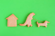 Leinwanddruck Bild - Homemade shortbread cookies on green background, top view. Dinosaur is walking with dog near house.