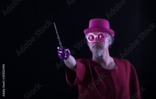 Photo male wizard with a magic wand on a black background